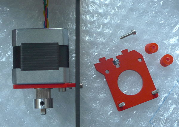 The Y-axis stepper and GT2 pulley installed. The remaining parts for this step are shown on the right